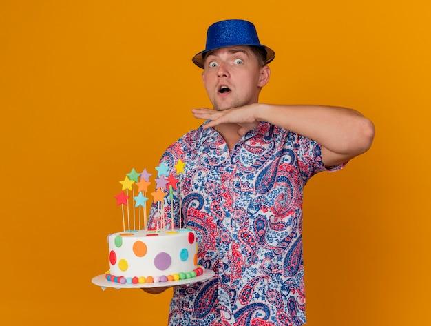 Verraste jonge partij kerel die blauwe hoed draagt die cake houdt en hand op keel zet die op oranje wordt geïsoleerd