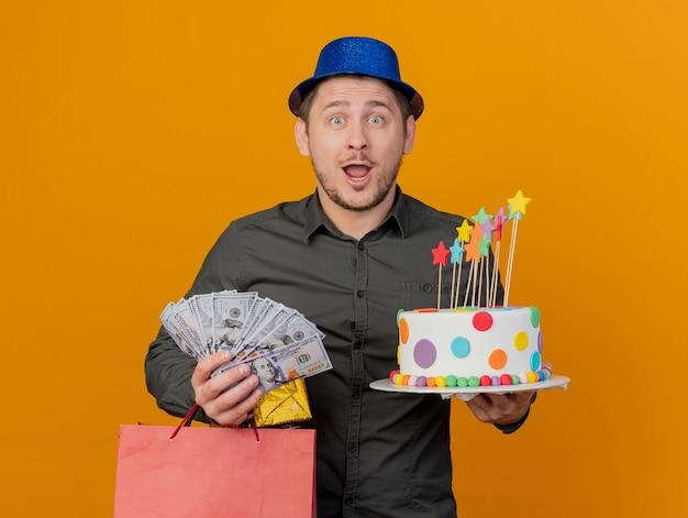 Verraste jonge partij kerel die blauwe hoed draagt die cake met giftzakken en contant geld houdt dat op oranje wordt geïsoleerd