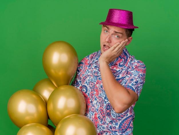 Verraste jonge partij kerel die roze hoed draagt ?? die ballons houdt die hand op wang zetten die op groen wordt geïsoleerd