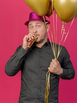 Verraste jonge partij kerel die roze hoed draagt die ballons houdt en partijventilator blaast die op roze wordt geïsoleerd