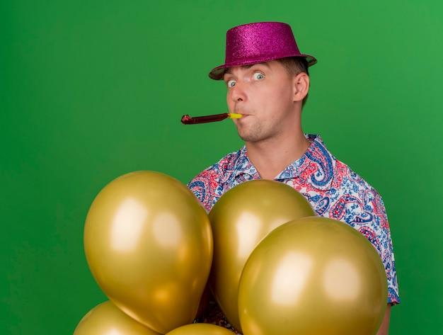 Verraste jonge partij kerel die roze hoed draagt die zich achter ballons bevindt en partijventilator blaast die op groen wordt geïsoleerd