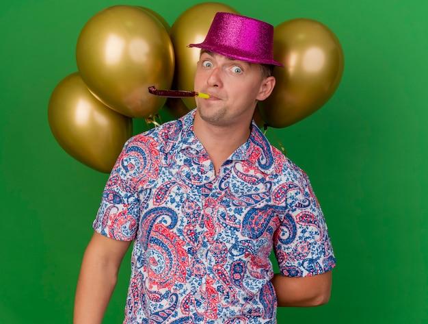 Verraste jonge partij kerel die roze hoed draagt die zich voor ballons bevindt en partijventilator blaast die op groen wordt geïsoleerd