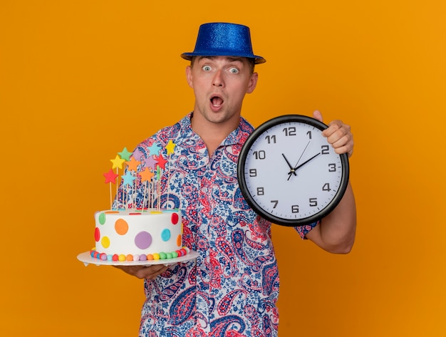 Verraste jonge partijkerel die blauwe de muurklok van de hoedenholding met cake draagt die op oranje wordt geïsoleerd