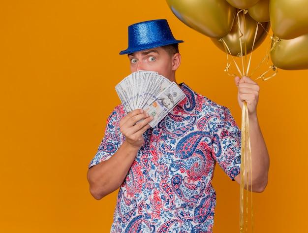 Verraste jonge partijkerel die blauwe hoed draagt die ballons houdt en bedekt gezicht met contant geld dat op oranje achtergrond met exemplaarruimte wordt geïsoleerd