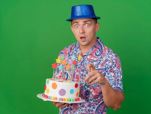 Verraste jonge partijkerel die de blauwe cake van de hoedholding draagt die u gebaar toont dat op groen wordt geïsoleerd