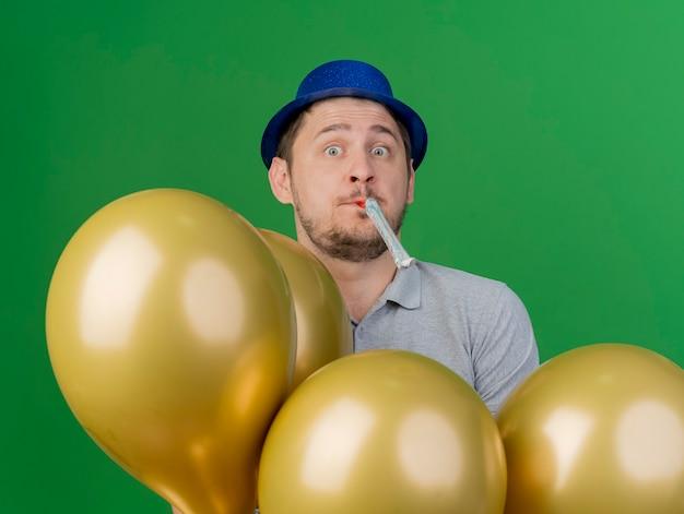 Verraste jonge partijkerel die partijhoed draagt die zich achter ballons blaast partijventilator die op groen wordt geïsoleerd