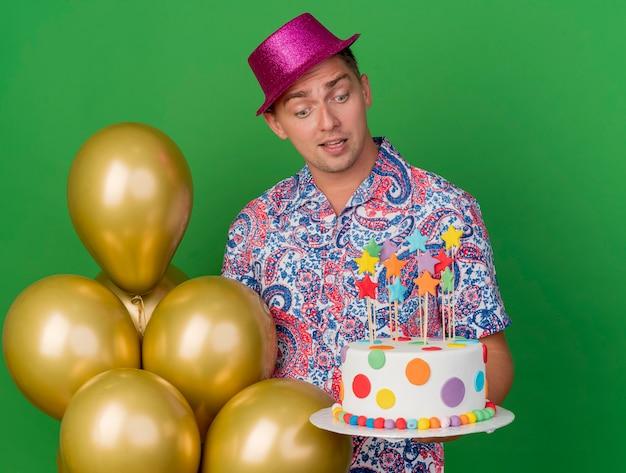Verraste jonge partijkerel die roze hoed draagt die zich naast ballons bevindt die en cake houdt die op groen wordt geïsoleerd