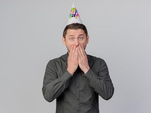 Verraste jonge partijkerel die verjaardags glb bedekte mond met handen draagt die op witte achtergrond wordt geïsoleerd