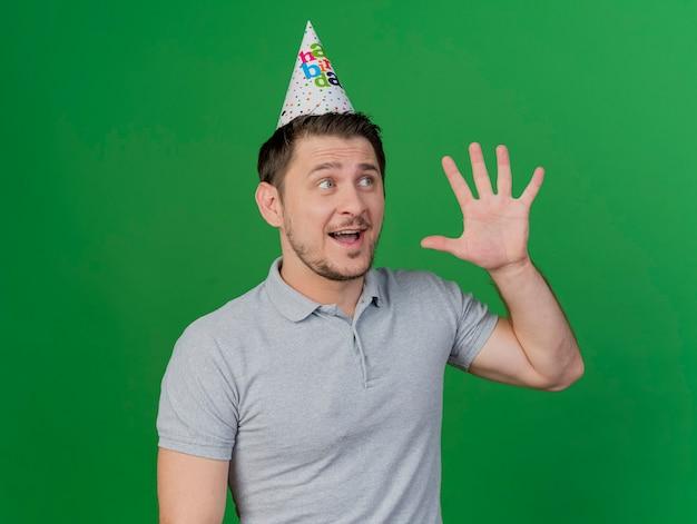 Verraste jonge partijkerel die verjaardags glb draagt die vijf op groen toont