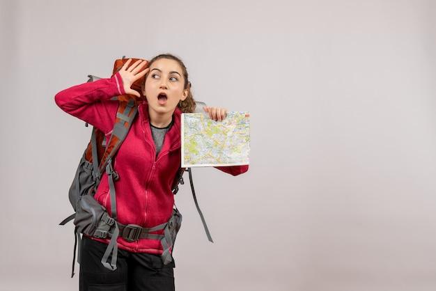 Verraste jonge reiziger met grote rugzak die kaart op grijs houdt