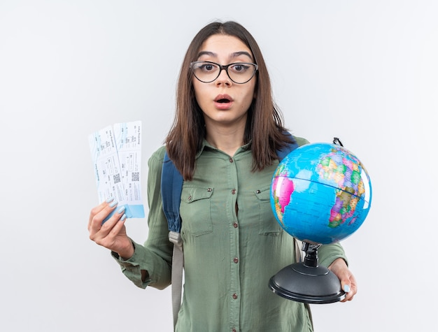 Verraste jonge reizigersvrouw die een bril draagt met een rugzak met een wereldbol met kaartjes