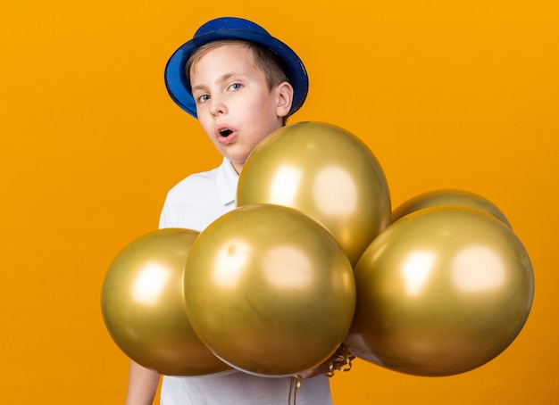 Verraste jonge slavische jongen met blauwe feestmuts die staat met heliumballonnen geïsoleerd op een oranje muur met kopieerruimte