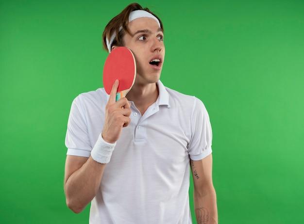 Verraste jonge sportieve kerel die kant bekijkt die hoofdband met polsband draagt die pingpongracket bij gezicht zet dat op groene muur wordt geïsoleerd