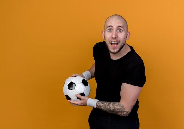 Verraste jonge sportieve man die de bal van de polsbandholding draagt ?? die op oranje muur met exemplaarruimte wordt geïsoleerd