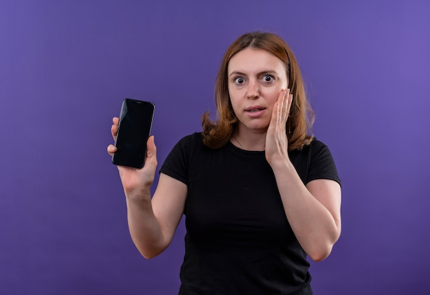 Verraste jonge toevallige vrouw die mobiele telefoon houdt en hand op wang legt op geïsoleerde purpere muur met exemplaarruimte