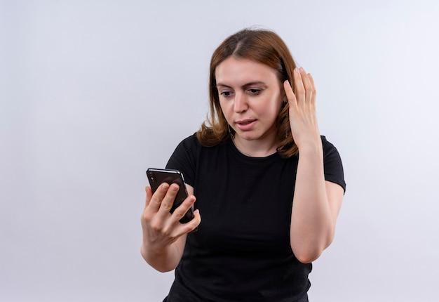 Verraste jonge toevallige vrouw die mobiele telefoon houdt en het met hand dichtbij hoofd op geïsoleerde witte muur met exemplaarruimte bekijkt