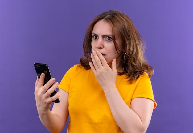 Verraste jonge toevallige vrouw die mobiele telefoon met hand op mond op geïsoleerde purpere muur houdt
