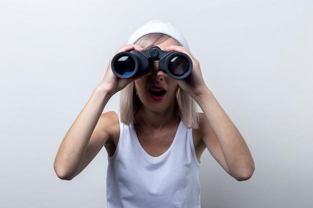 Verraste jonge vrouw die door een verrekijker op een lichte achtergrond kijkt.