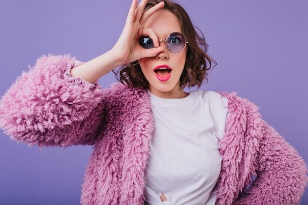 Verraste jonge vrouw die in pluizig jasje gezichten op purpere muur maakt. spectaculair wit meisje in zonnebril gek rond.