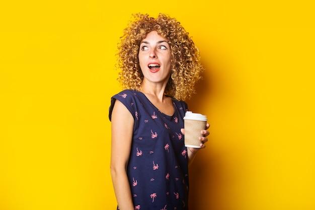 Verraste jonge vrouw die met krullend haar document kop op gele oppervlakte houdt
