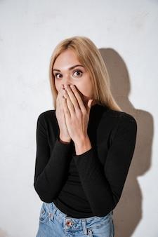 Verraste jonge vrouw die mond behandelt met handen