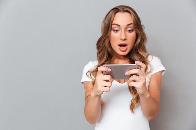 Verraste jonge vrouw die op smartphone kijkt die op een grijze muur wordt geïsoleerd