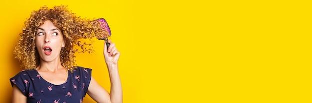 Verraste jonge vrouw die verward krullend haar op gele achtergrond kamt.