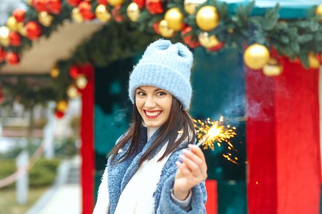 Verraste jonge vrouw draagt blauwe jas en geniet van vakantie met bengaalse lichten