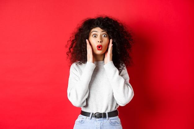 Verraste jonge vrouw hoort geweldig nieuws, kijkt naar promo en zegt wow, staart met ongeloof, staande op rode achtergrond