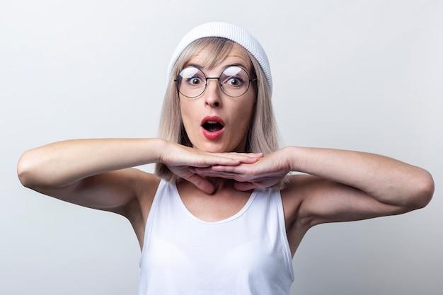 Verraste jonge vrouw houdt haar handpalmen onder haar kin op een lichte achtergrond.
