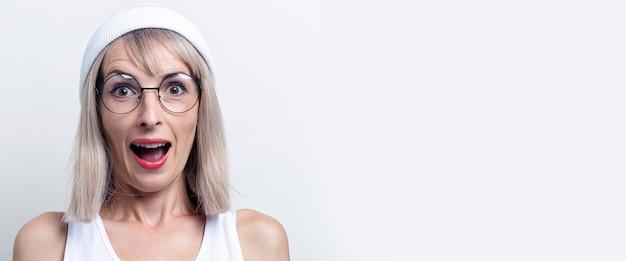 Verraste jonge vrouw in een witte hoed en bril op een lichte achtergrond. banier.