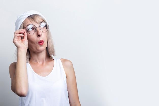 Verraste jonge vrouw in een witte hoed en bril op een lichte achtergrond.