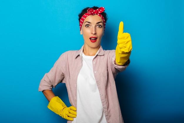 Verraste jonge vrouw in het schoonmaken van handschoenen die duim op gebaar, klassengebaar op blauwe oppervlakte tonen