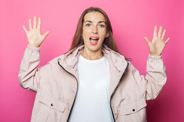 Verraste jonge vrouw in roze jasje, roze geïsoleerde achtergrond.
