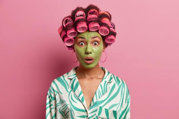 Verraste jonge vrouw kijkt stomverbaasd, nonchalant gekleed, ondergaat schoonheidsprocedures en maakt perfecte haarstijlen, maakt zich klaar voor feest, wil er mooi uitzien, geïsoleerd op roze muur