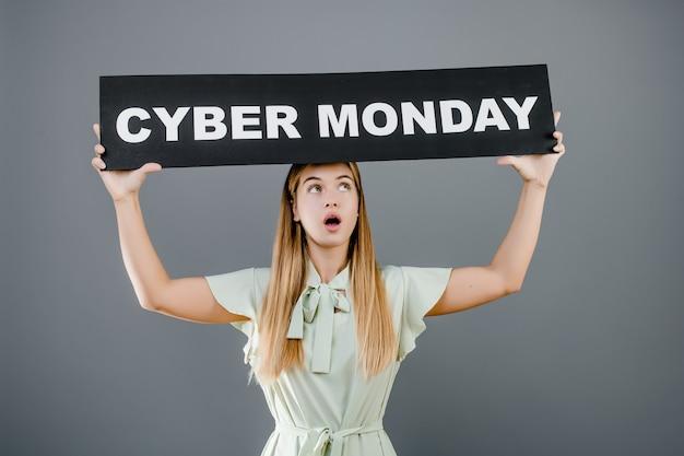Verraste jonge vrouw met het teken van de cybermaandag dat over grijs wordt geïsoleerd