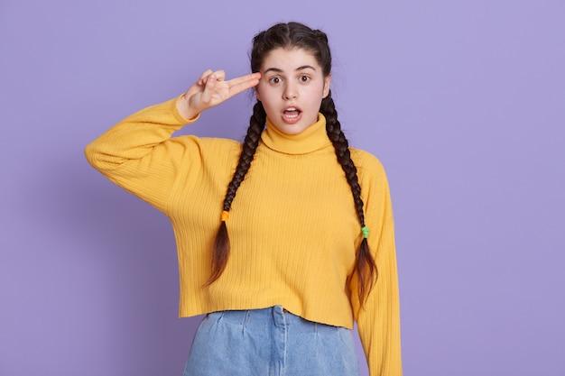 Verraste jonge vrouw met staartjes, kleedt gele trui, houdt haar mond open en staat met haar vingers bij de tempel als geweer