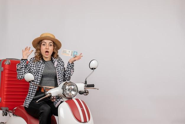 Verraste jonge vrouw op bromfiets die kaartje op grijs houdt