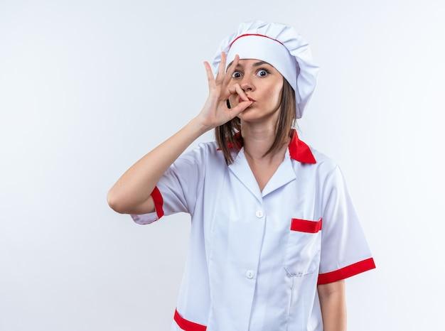 Verraste jonge vrouwelijke kok die chef-kokuniform draagt die heerlijk gebaar toont dat op witte muur wordt geïsoleerd