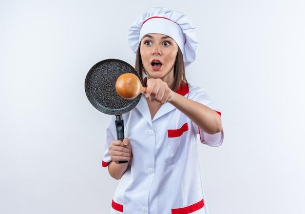 Verraste jonge vrouwelijke kok die chef-kokuniform draagt die pan met lepel houdt die op witte muur wordt geïsoleerd
