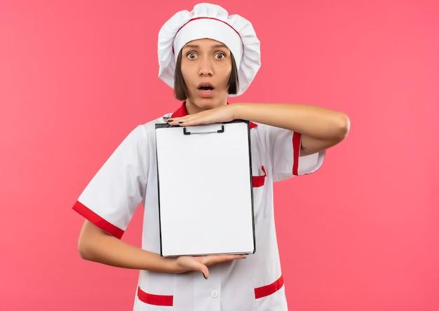 Verraste jonge vrouwelijke kok die in het klembord van de chef-kok het eenvormige holding voorzijde bekijkt die op roze muur wordt geïsoleerd