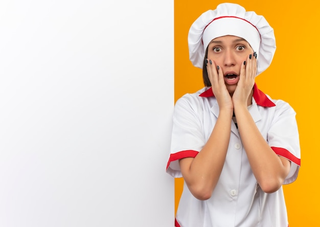 Verraste jonge vrouwelijke kok in eenvormige chef-kok die zich voor witte muur bevindt die handen op gezicht zet dat op oranje muur wordt geïsoleerd