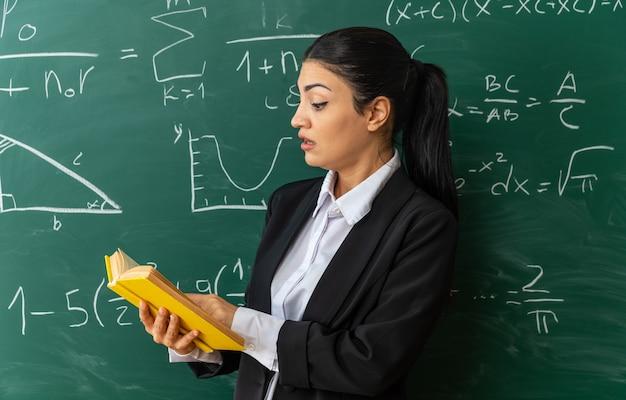 Verraste jonge vrouwelijke leraar die vooraan schoolbord leesboek in de klas staat