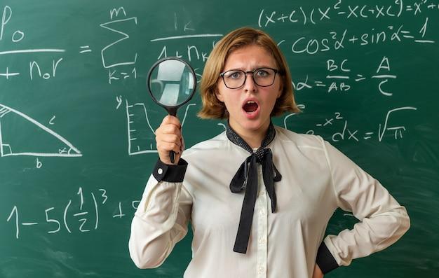 Verraste jonge vrouwelijke leraar met een bril die voor het schoolbord staat met een vergrootglas en de hand op de heup zet in de klas