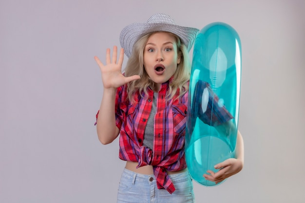 Verraste jonge vrouwelijke reiziger die rood overhemd in hoed draagt die opblaasbare ring houdt die stopgebaar op geïsoleerde witte muur toont