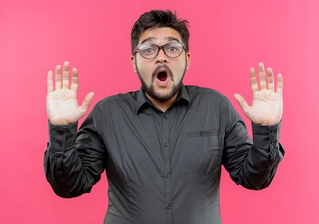 Verraste jonge zakenman die glazen draagt die handen opheffen die op roze worden geïsoleerd