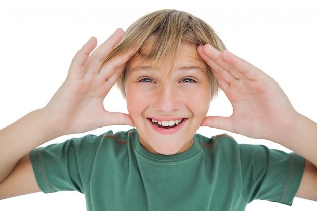 Verraste jongen die met opgeheven handen glimlacht