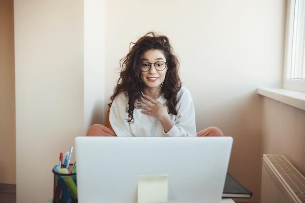 Verraste kaukasische student met oogglazen die een online les met laptop hebben