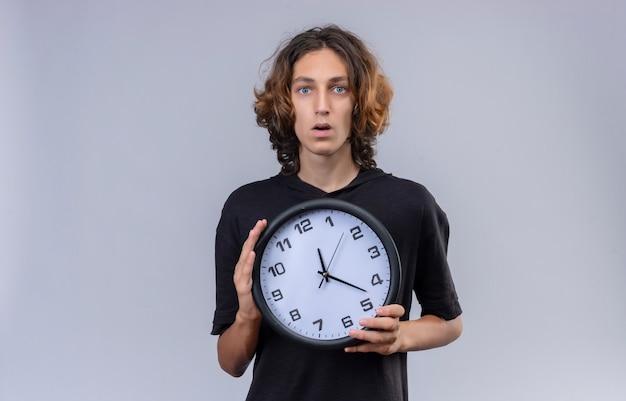Verraste kerel met lang haar in zwart t-shirt een muurklok op witte achtergrond