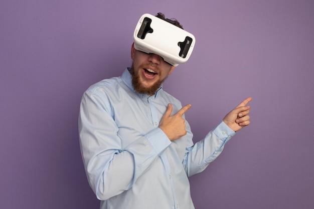 Verraste knappe blonde man met vr-headset wijst aan de zijkant met twee handen geïsoleerd op paarse muur